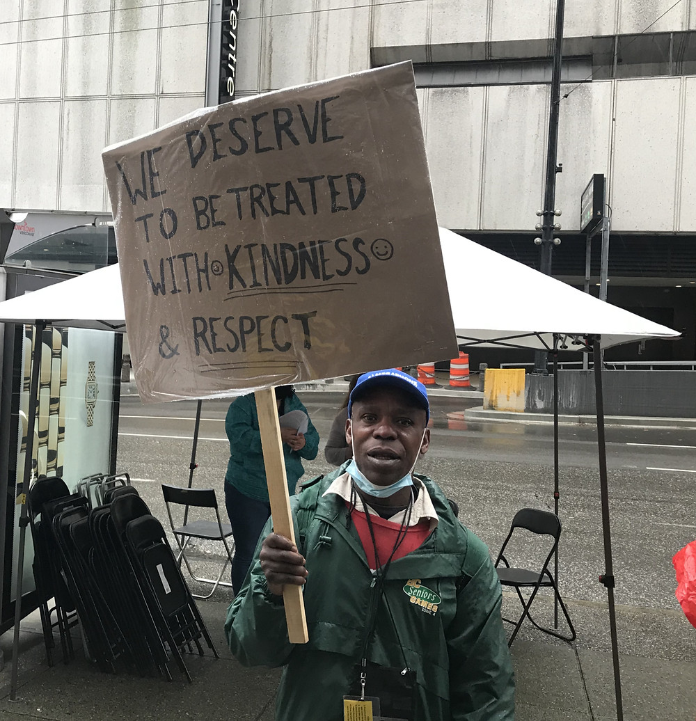 """Man holding sign that says """"We deserve to be treated with kindness and respect"""""""