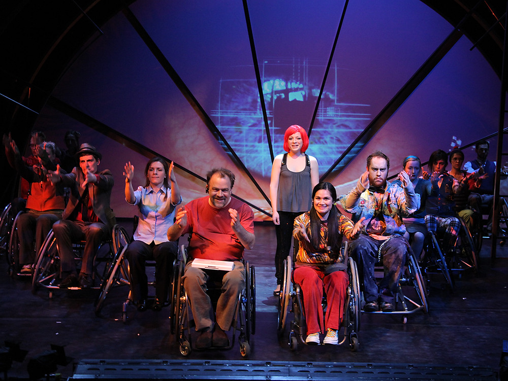 A group of actors in wheelchairs perform on stage