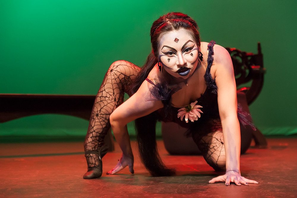 Opera Mariposa's Jacqueline Ko, with elaborate white and black makeup, crouches during a performance