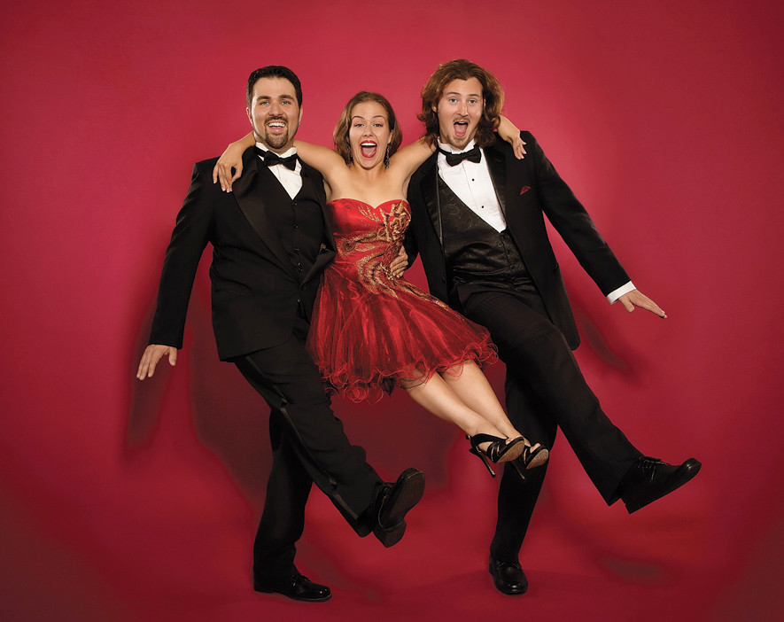 Robin Hahn of Opera Mariposa, dressed in a red dress, is lifted by two men in tuxedos, as part of Don Pasquale!