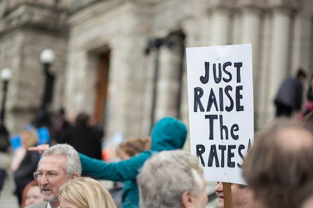 Person holding sign that says 'just raise the rates'