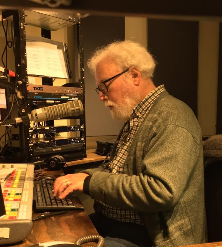 Victor, with white hair and a glorious white beard, sits at a desk in a radio studio, helping produce a radio show