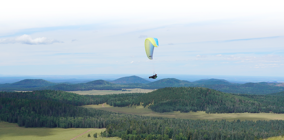 John Wolfe flying a paraglider, illustrating that Maile Technical helps take software-development productivity to new heights