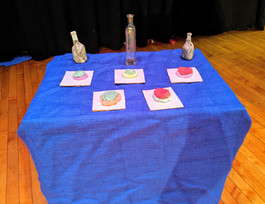 Image description: A table with a blue tablecloth decorated with props created by students: bottles and pastries for the party scene in Romeo and Juliet.
