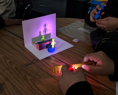 Image description: Students use LED flashlights, gel swatches, and figurines to experiment with lighting design on a small scale.