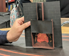 Image description: A student holds their model of a fireplace, created as part of a set design residency.