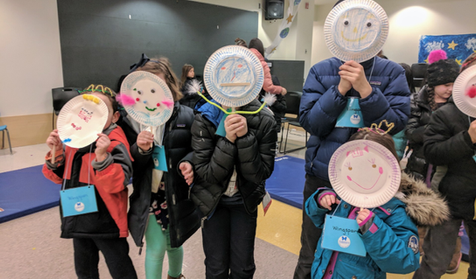 Image description: Students wear the paper plate masks they created during a pre-show worksho for Isle Full of Noises