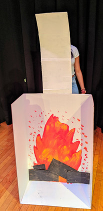 Image description: A fireplace designed and constructed by a student using a cardboard box and paint.
