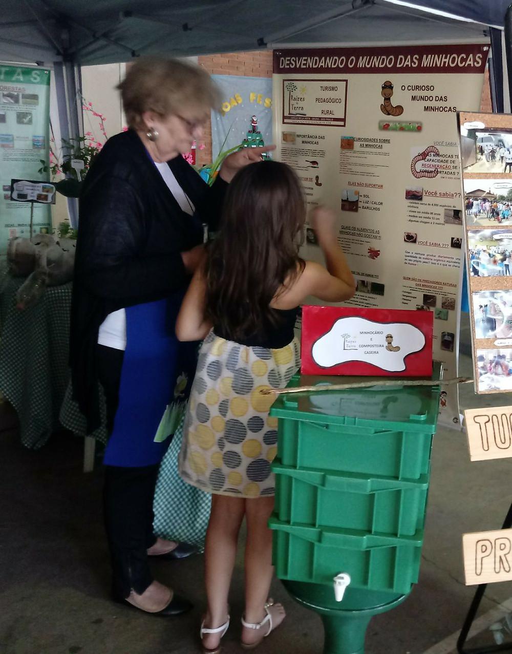 Ilda apresentando o mundo das minhocas para a pequena visitante interessada