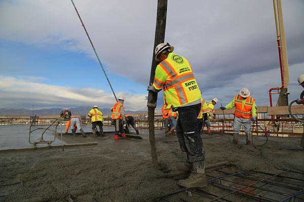 Laborers pouring concrete