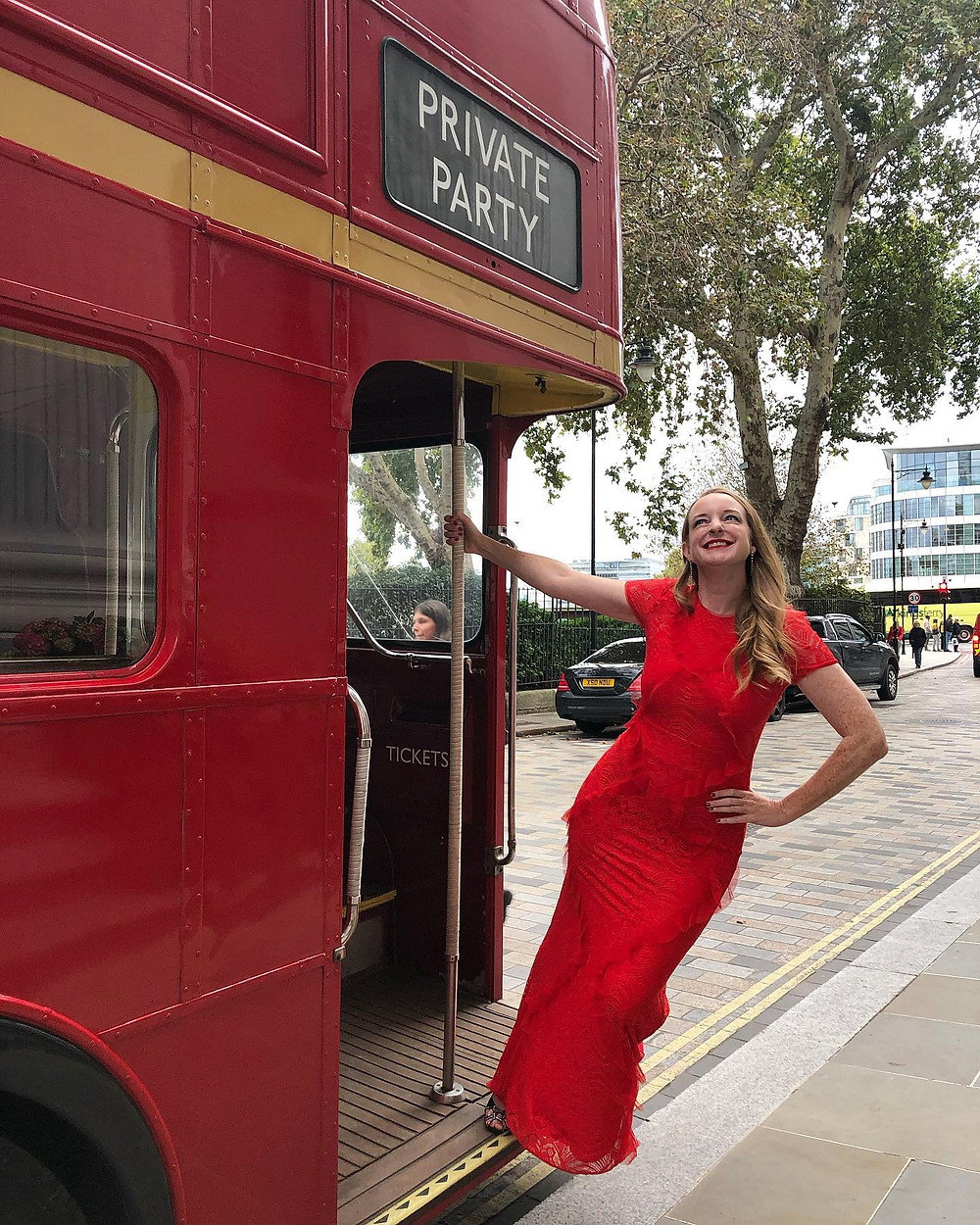 Nicola Chilton in red dress on a traditional red London bus