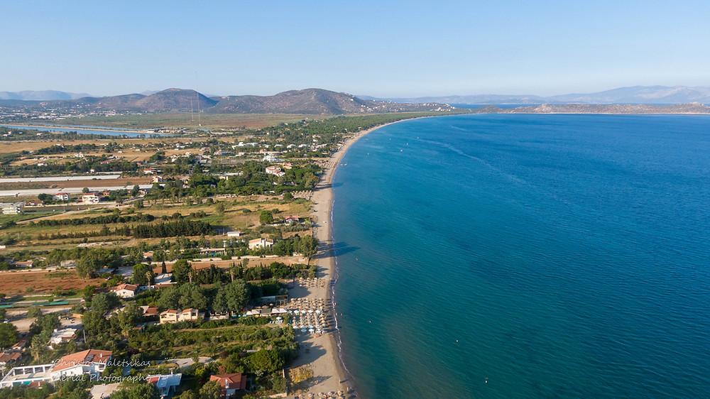 Η αμμώδης παραλία του Σχινιά και στο βάθος αριστερά διακρίνεται το Κωπηλατοδρόμιο | Φωτ.: Χρήστος Μαλέτσικας