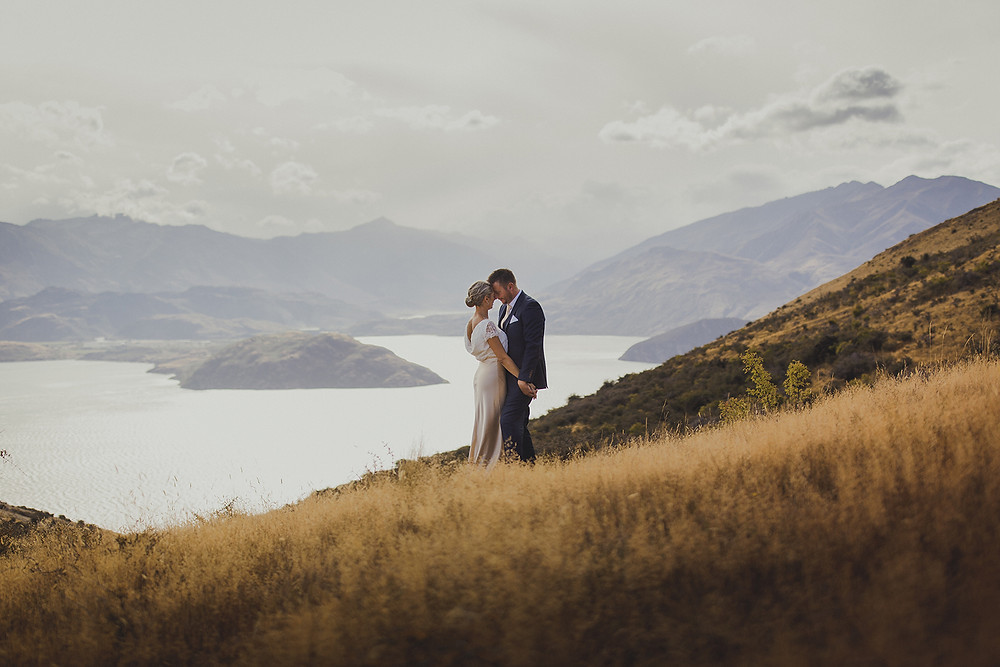 Groom and bride, wearing Margaret Wray Lily wedding gown standing on a mountain overlooking lake in Central Otago, New Zealand