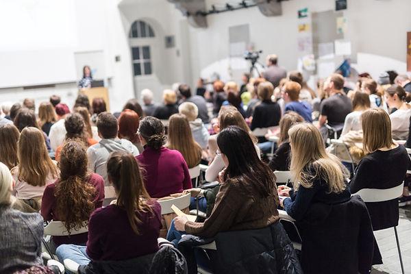 Female speaker giving presentation in le