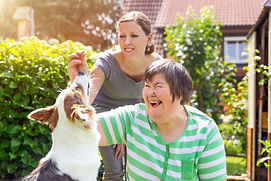 A support worker helping disabled person with daily activities such as feeding dog