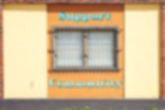 Orange-yellow building with a window. The window has white blinds and a grill. 'Support Community' is painted on the facade in turquoise. Image by Matthew Schwartz.
