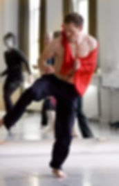 Conscious dance with Jess Glenny at Embody in south-east London. Dancer in black trousers, bare chest, with red coth over his chest, standing on one leg in mid movement.