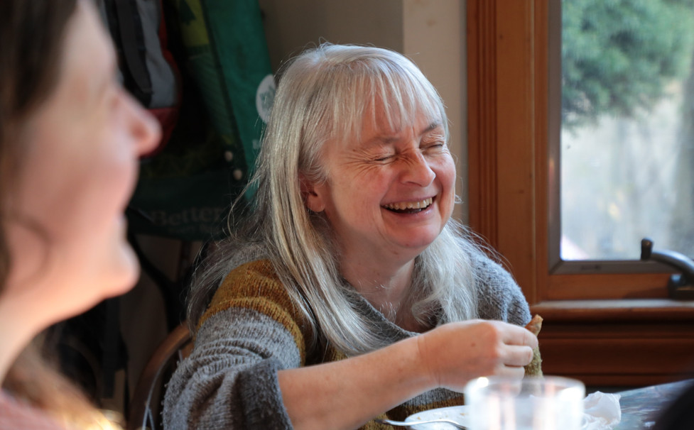 CRECHE member laughing at house meal