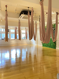 This picture is showing the interior design of Moment Yoga studio in Central, Hong Kong. The floor is wooden floor. There is a greenery wall having a LED Moment Yoga's logo signboard on it. Nice and neat place and 11 sets of aerial hammock are found. Windows are large and the room is bright with adequate sunlight.