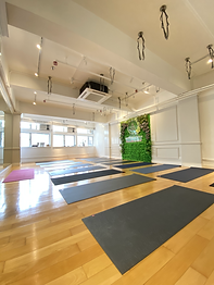 This picture is showing the interior design of Moment Yoga studio in Central, Hong Kong. The floor is wooden floor. There is a greenery wall having a LED Moment Yoga's logo signboard on it. Nice and neat place and 18 yoga mats are found. Windows are large and the room is bright with adequate sunlight.