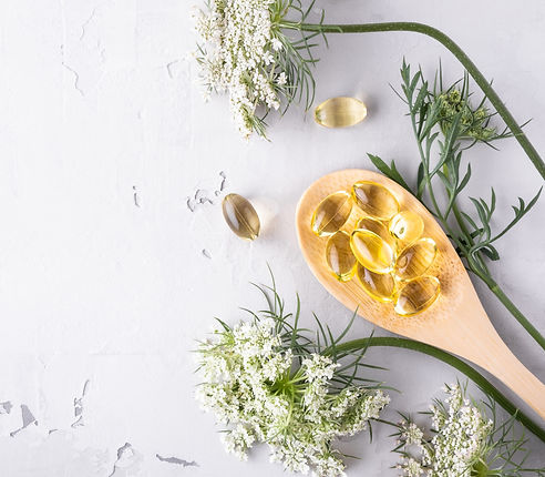 supplements on wooden spoon and flowers