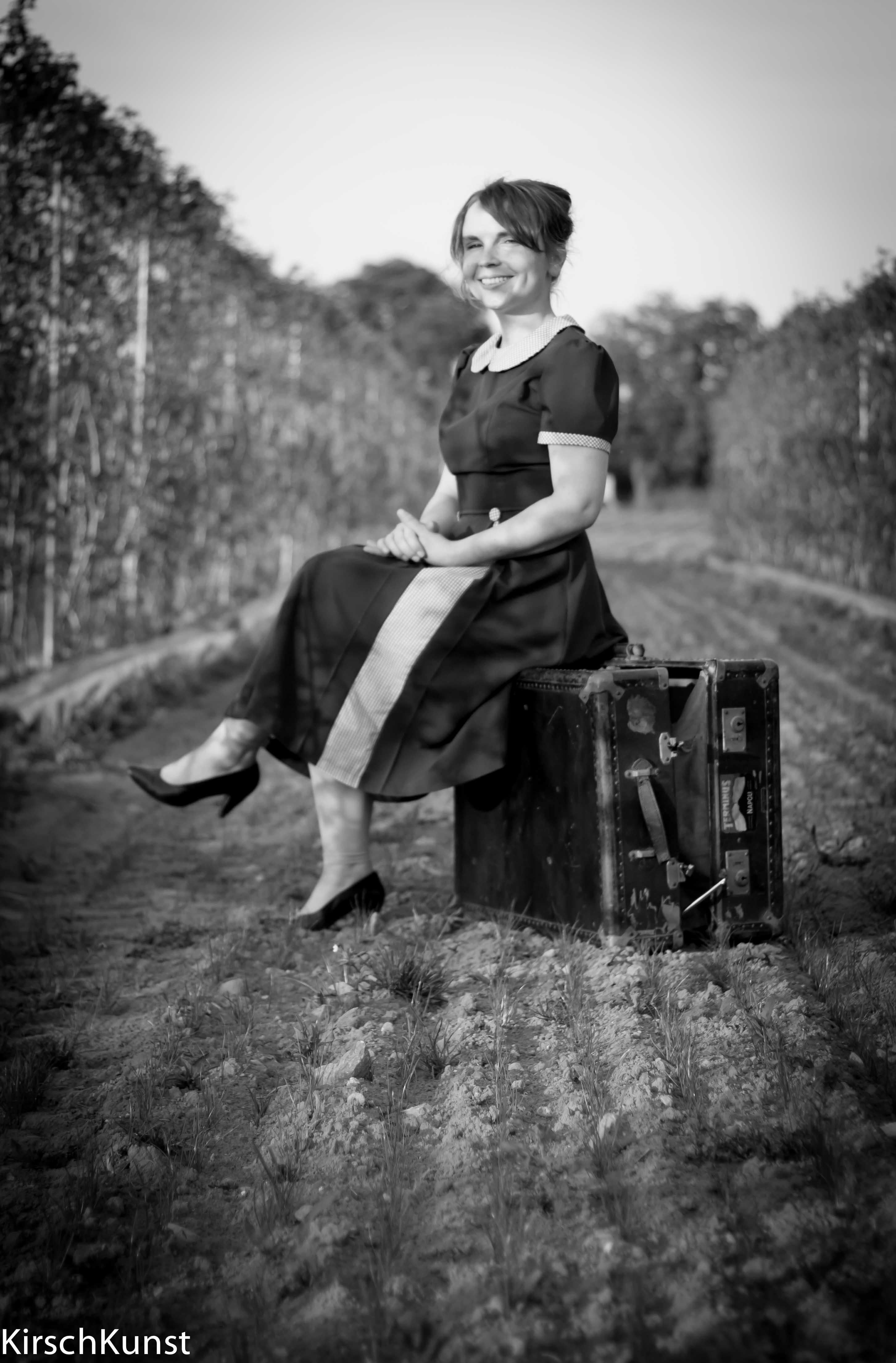 Frau im Feld auf einer Kiste sitzend