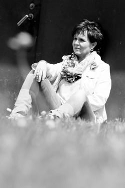 Frau sitzt auf einer Wiese