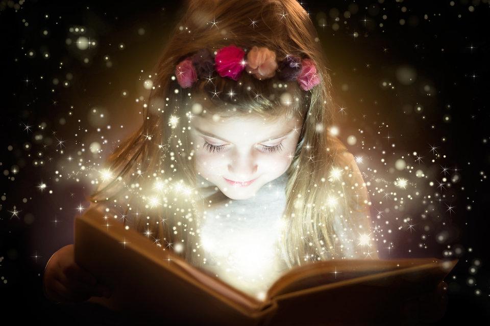 Pretty little girl reading magic book.jp