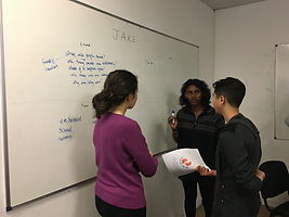 Three students standing in front of a whiteboard, working through one of our workshops.