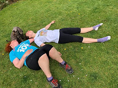 Two people lie down on the grass after completing a 10k.