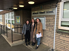Beth, Laura, and Anna, three LUNA team members, stod outside a school in which they have just delivered a workshop