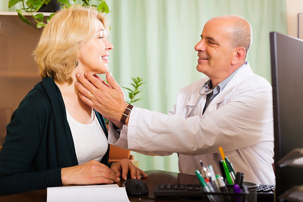 mature-doctor-checking-thyroid-smiling-w