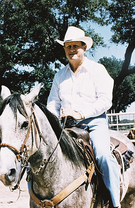 Red McCombs out on his ranch riding a horse