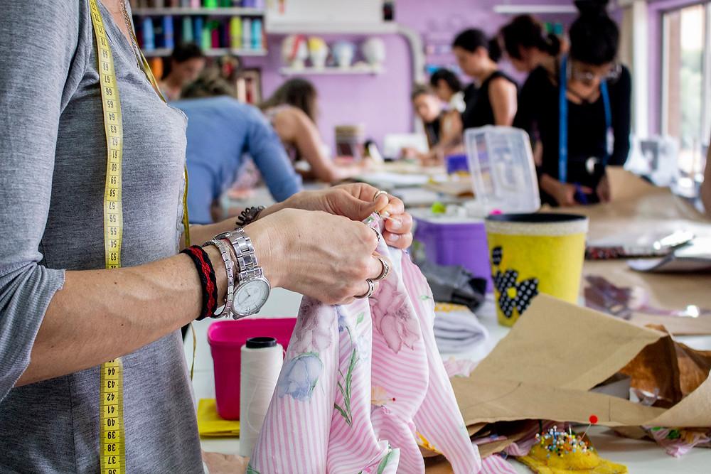 mulher costurando, costurando, utilizando a fita métrica.