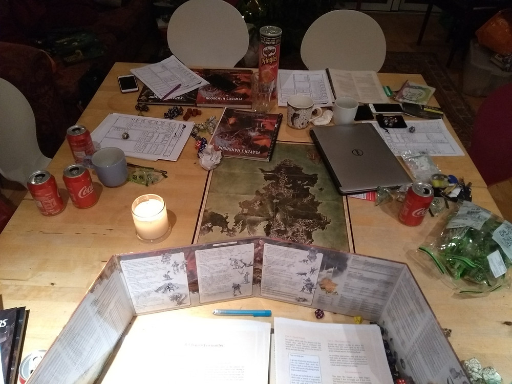 A table set up for Dungeons and Dragons, from the GM perspective, showing a map, notes, soda cans, DM screen, and snacks.