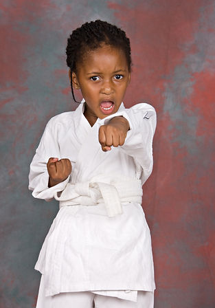 Small karate girl training , on colorful