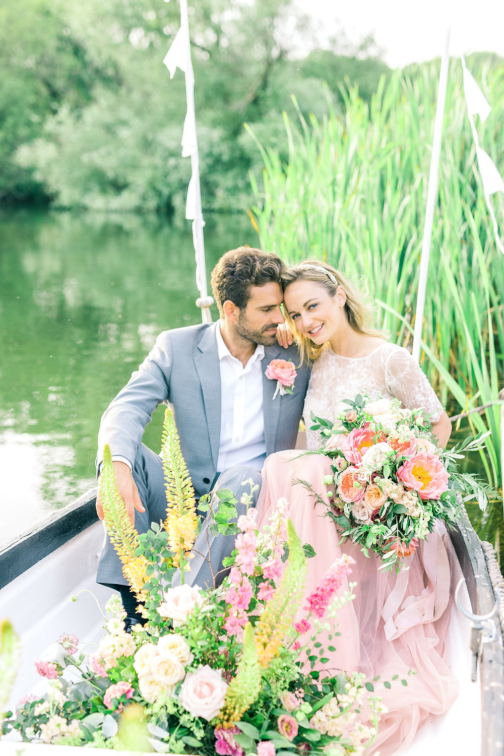 Lake photo of wedding flowers with bride and groom