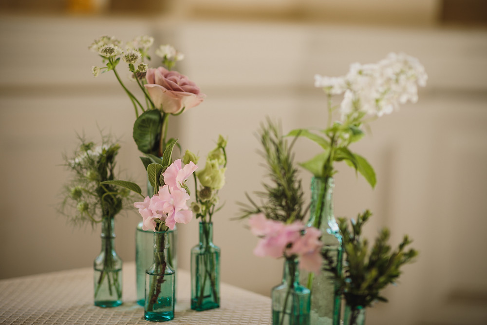Vintage bottles, filled with romantic flowers and fragrant herbs for the ceremony table