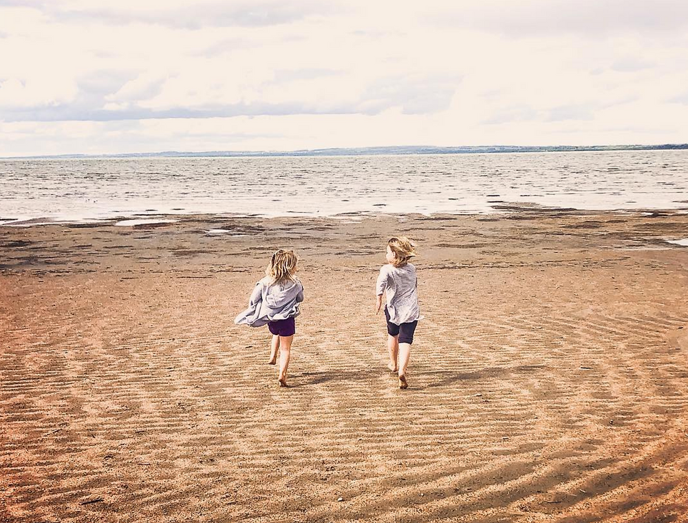 Photo of kids running on Gull Lake Beach.
