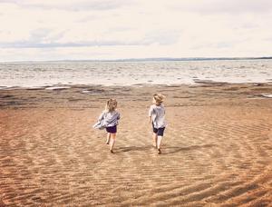 Photo of kids running on Gull Lake Beach.