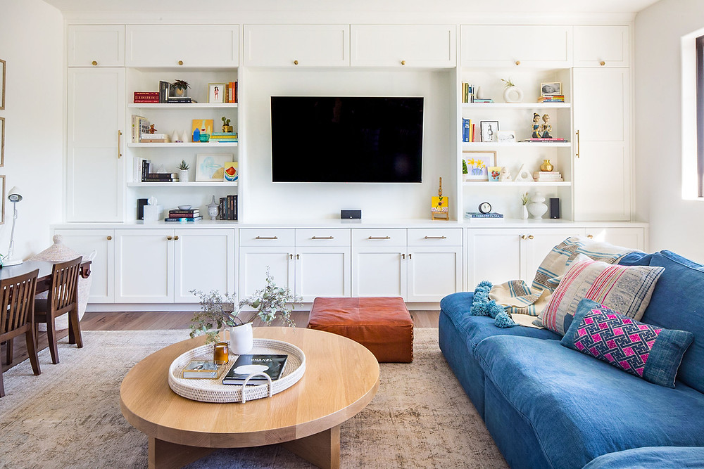 Built in white bookcase in family room with blue sofa