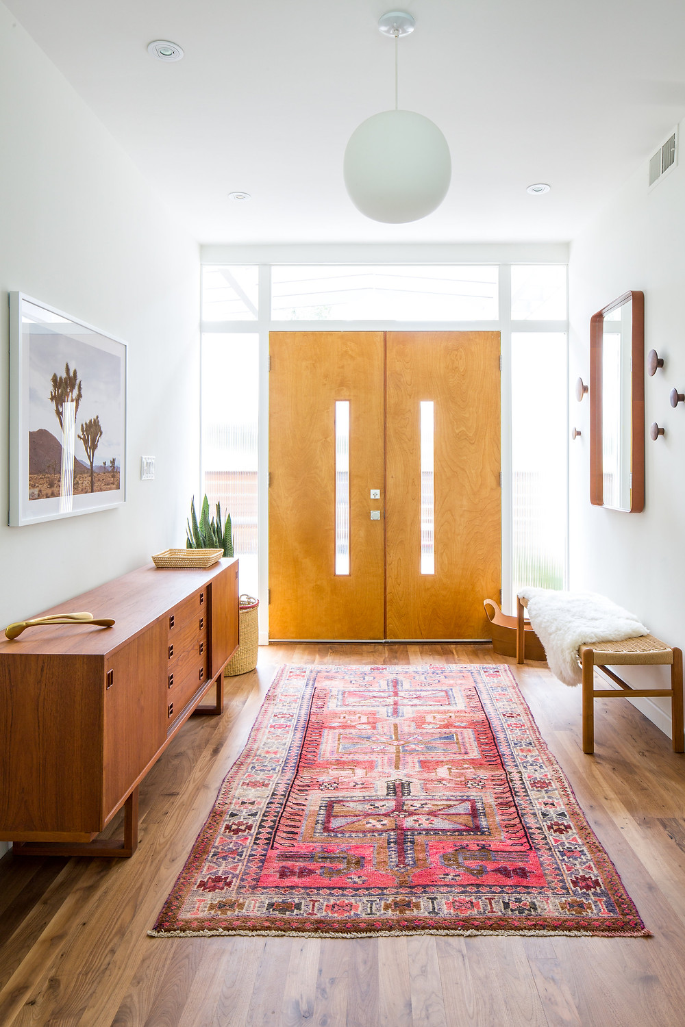 Midcentury modern entry way with double doors and vintage rug