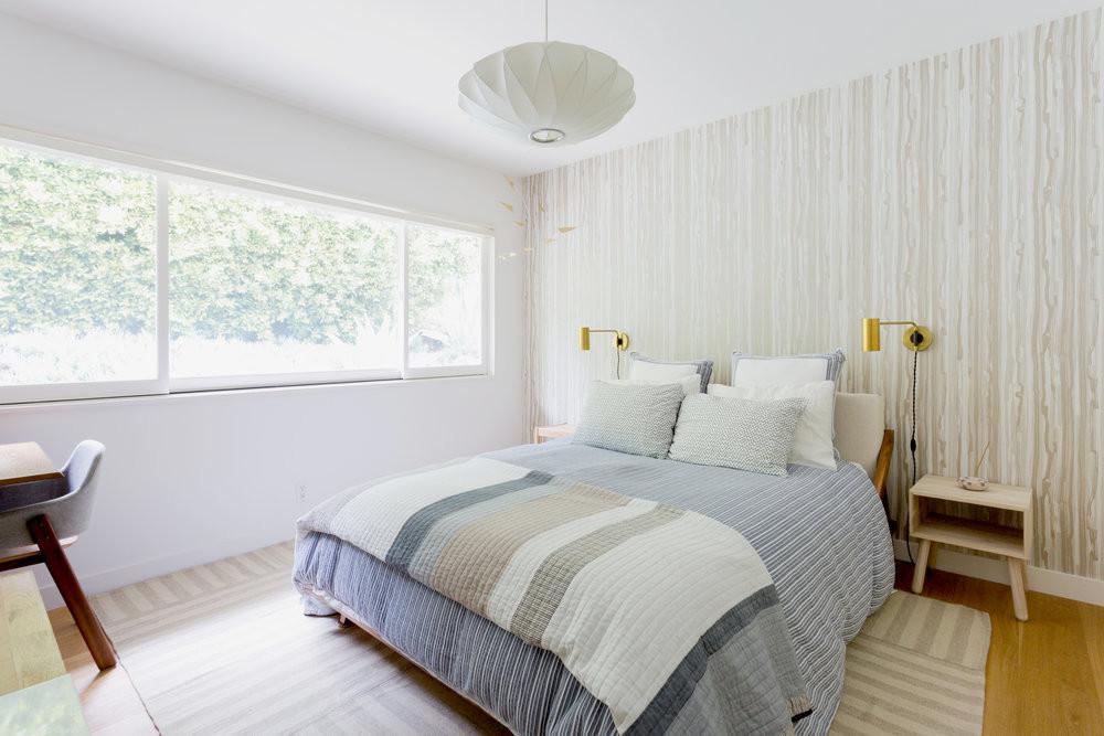 Soothing guest bedroom with platform bed and organic hued wallpaper by Veneer Designs