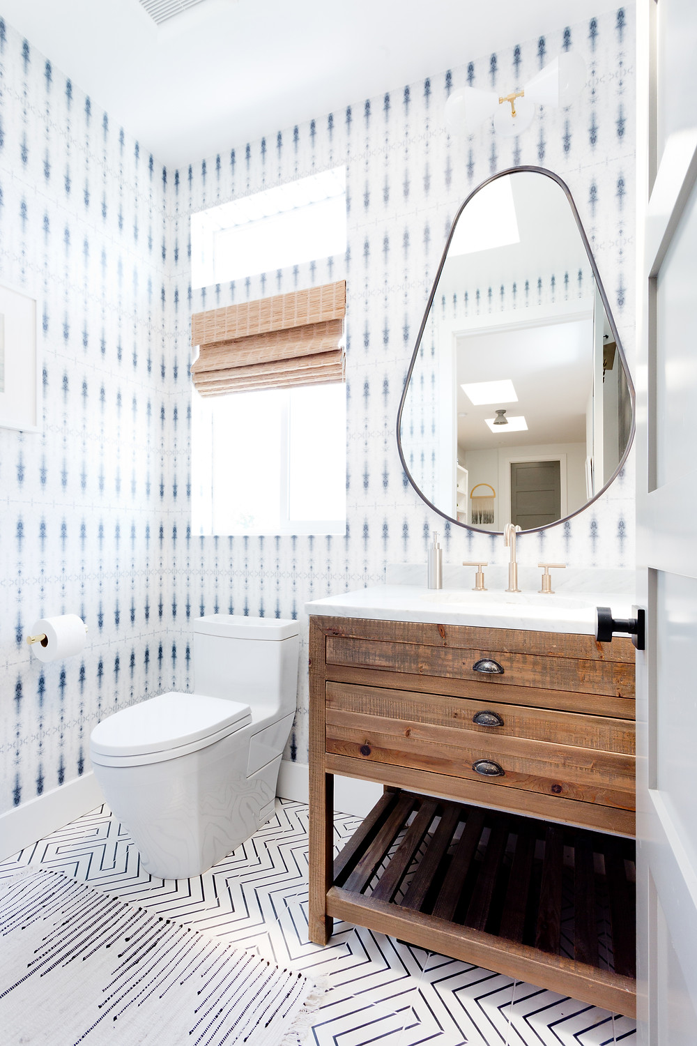 A mix og wallpaer and floor tile patterns in a beachy powder room by Veneer Designs