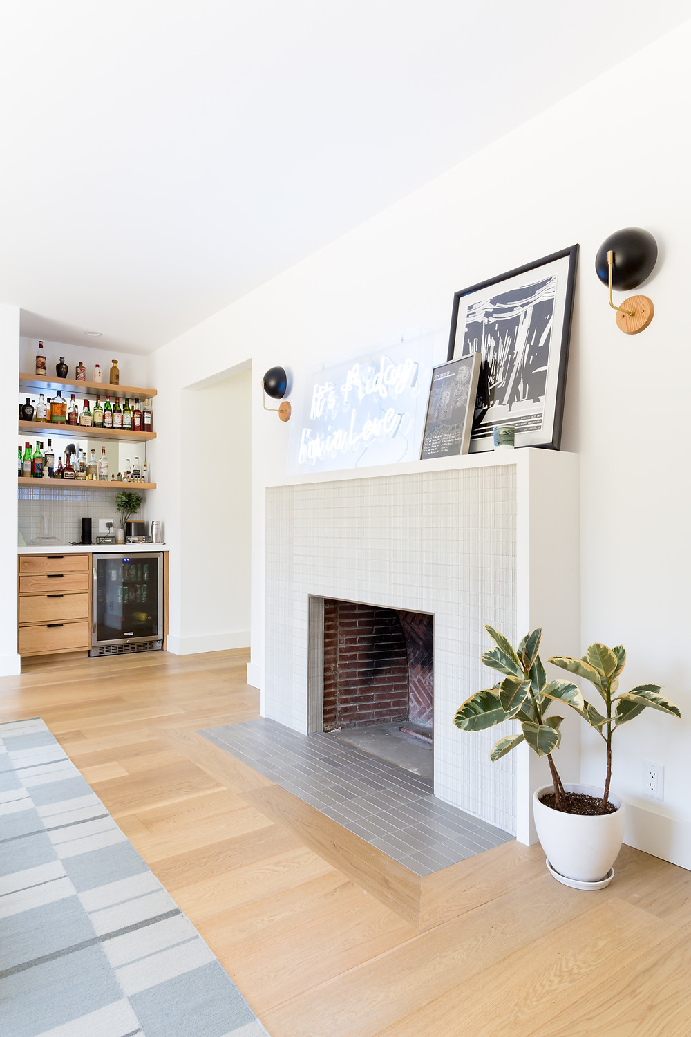 Tiled fireplace with a vew to the home bar in a living room designed by Veneer Designs