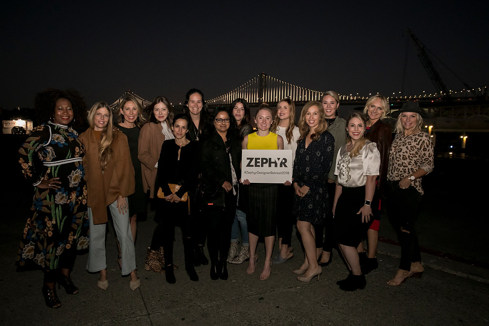 Designer group shot in front of the Golden Gate bridge at night