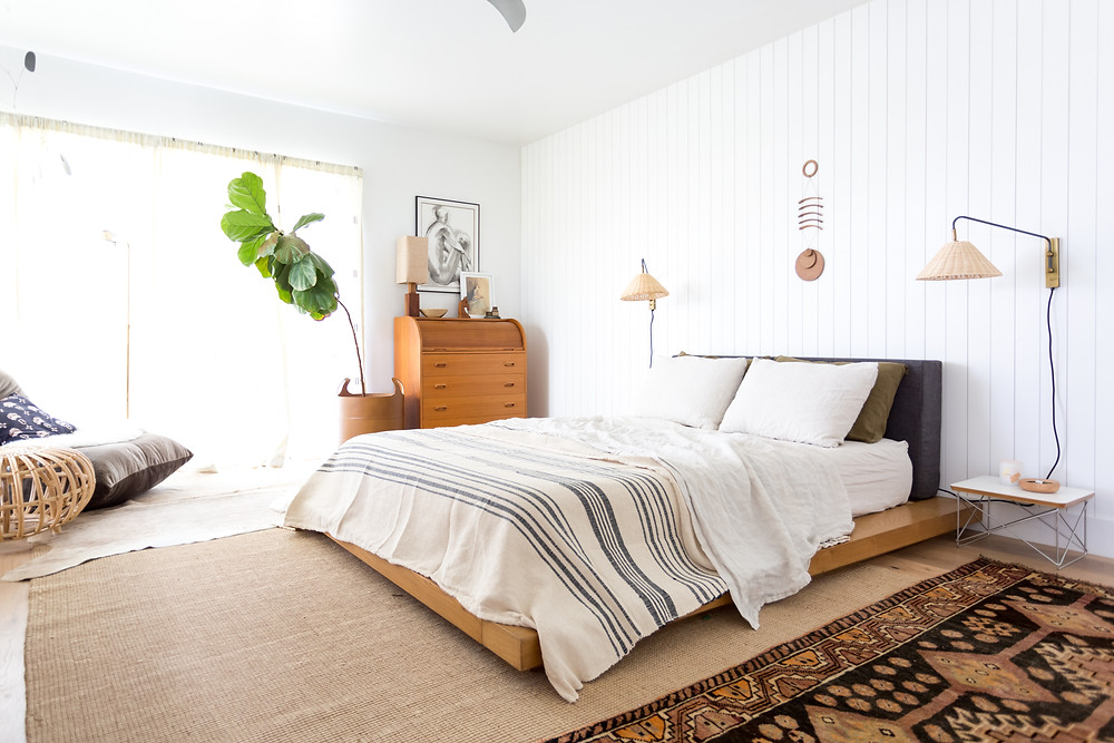 Low platform bed and vertical shiplap accent wall in a bedroom by Veneer Designs