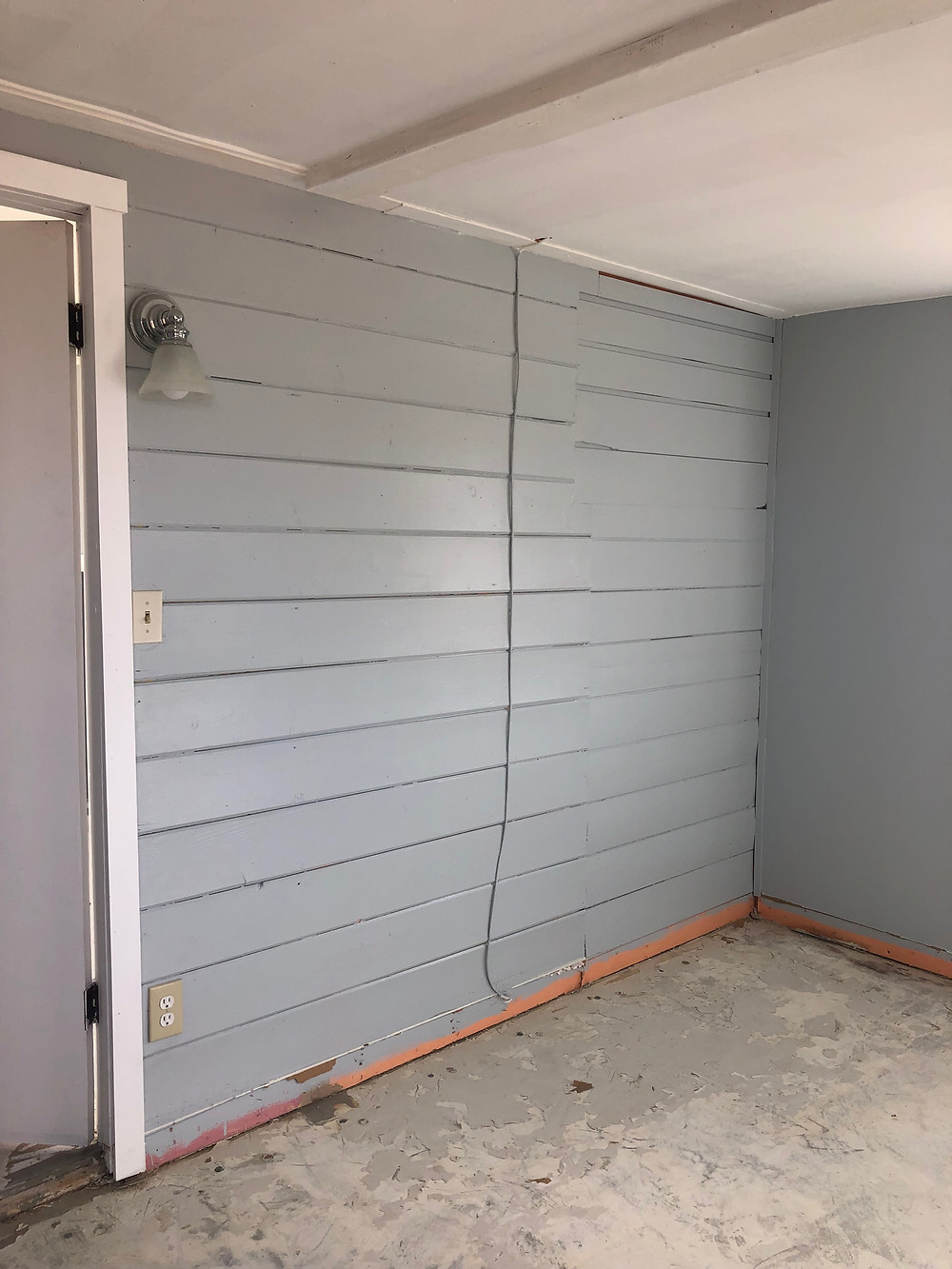 Bedroom before picture with exterior siding on wall