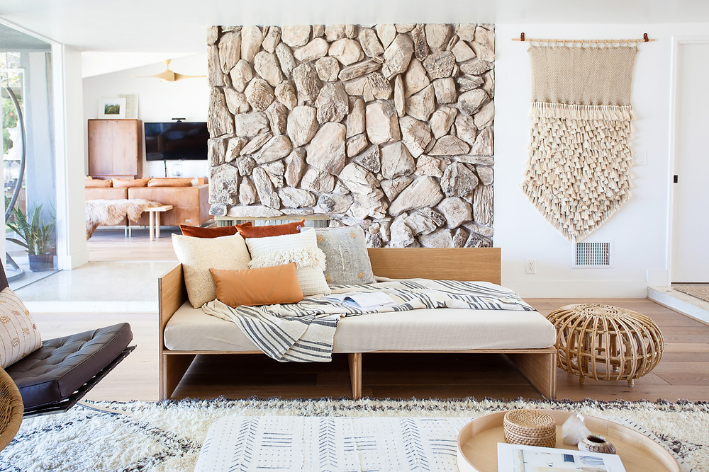 Plywood daybed in front of vintage lava rock fireplace