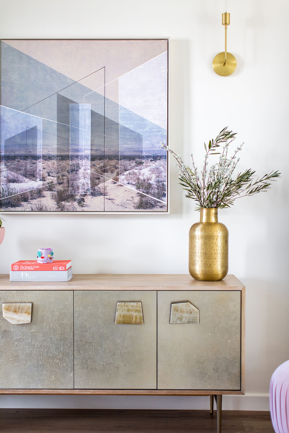 Vignette of vase and art over console cabinet styled by Veneer Designs